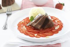 Chocolate cake on strawberry carpaccio with vanilla ice cream Stock Photos
