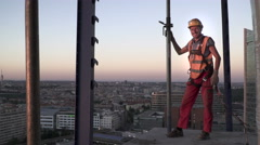 High construction  worker is standing on  talle building after hard work Stock Footage