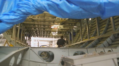 Worker inside fuselage mounts to luggage compartment Stock Footage