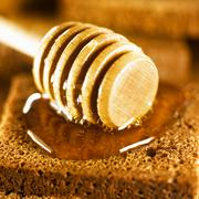 Honey dipper and honey on wholemeal bread Stock Photos