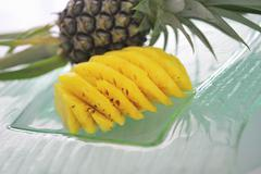 Baby pineapples, unpeeled and peeled and sliced Stock Photos