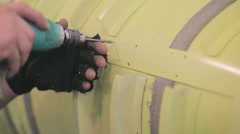 Employee aircraft manufacturing plant drills holes in fuselage of aircraft Stock Footage