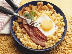 Fried egg and bacon on chick-peas Stock Photos