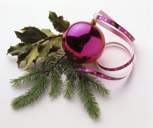 Pink Christmas bauble with sprigs of fir and holly Stock Photos