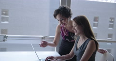 Business women collaborate happily on laptop in urban loft 4K Arkistovideo