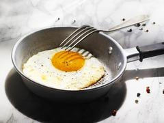 Fried egg in a small frying pan Stock Photos