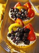 Two berry and kiwi fruit tartlets Stock Photos