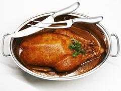 Roast goose in roasting dish, carving knife and fork Stock Photos