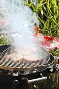 Pork steaks on smoking barbecue out of doors Stock Photos