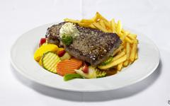 Rump steak with chips and summer vegetables Stock Photos