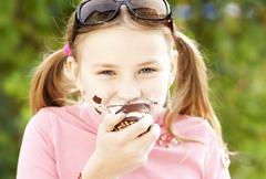 A girl eating a chocolate marshmallow Stock Photos