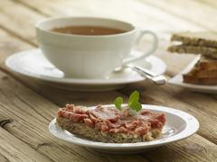Bread spread with Teewurst and a cup of tea Stock Photos