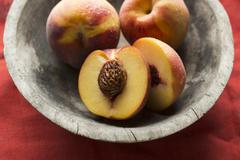 Fresh Peaches in a Bowl; Whole and Halved Stock Photos