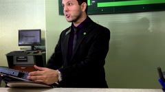 Bank clerk helping customer to deposit cheque inside TD bank Stock Footage