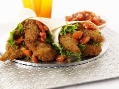 Breaded chicken fillets and tomato salsa wraps Stock Photos