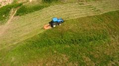 Aerial shot a farmer cutting grass on a field by ocean cove Stock Footage