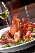 Whole Lobster with Fresh Greens on a Plate; Glass of Chardonnay Stock Photos