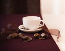 Chocolate Truffles and Wrappers with a Coffee Cup Stock Photos