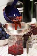 Homemade damson jam being transferred to glasses Stock Photos