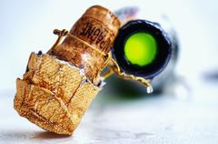 A champagne cork and an open bottle of champagne Stock Photos