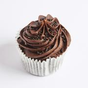 A chocolate cupcake on a white surface Stock Photos