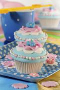 Light blue cupcakes decorated with pink flowers and sugar balls Stock Photos