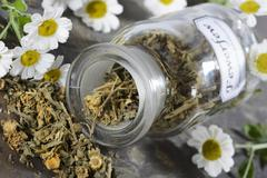 Dried feverfew in an apothecary bottle Stock Photos
