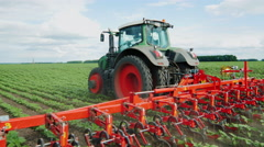 Steadicam fly around shot: Tractor pulls on the field, agricultural mechanism Stock Footage