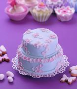 A two tier Easter cake decorated with blue icing and pink sugar flowers Stock Photos
