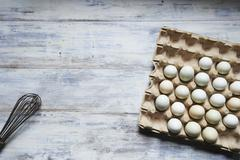 Fresh Pastel Colored Eggs in a Cardboard Carton on a Wooden Table; From Above Stock Photos