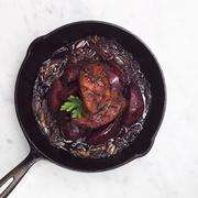 Duck and Poached Quince in a Cast Iron Skillet with Caramelized Onions Stock Photos