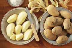 Potatoes, peeled and unpeeled Stock Photos