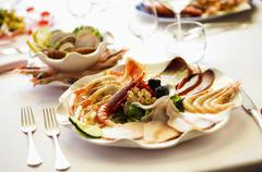 A plate of mixed starters with prawns, langoustines, and carpaccio of tuna and Stock Photos