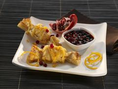 Pastry parcels with pomegranate and orange zest Stock Photos