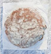 A loaf of bread on paper, on a marble slab, dusted with flour Stock Photos
