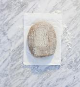 A loaf of bread on paper, on a marble surface, dusted with flour Stock Photos