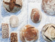 A variety of loaves, on paper and on a marble surface, dusted with flour Stock Photos