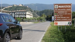 Marostica city sign with castle in background with cyclist and car passing Stock Footage