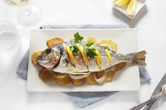 Grilled gilt-head bream with oranges on top of potato slices Stock Photos