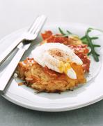 Potato and carrot fritter topped with a poached egg Stock Photos