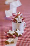 Star-shaped cinnamon biscuits and fabric stars in a mug Stock Photos
