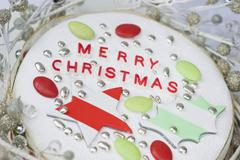 Christmas cake with striped stars and holly leaves, silver sugar candy beads and Stock Photos