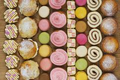 Rows of cupcakes, scones, macarons, Swiss rolls and pieces of mini-Battenburg Stock Photos