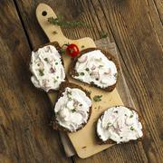 Slices of whole grain bread with quark and onions on a wooden board (top view) Stock Photos