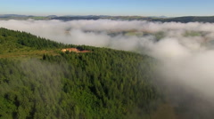 Aerial: backwards flight over excavated hill, green forest and clouds. Stock Footage