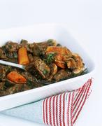 Beef casserole with carrots in a white dish with stripy tea towel white cut out Stock Photos