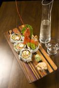 Lobster Sushi on a Wooden Platter; Pitcher and Glass of Sake Stock Photos