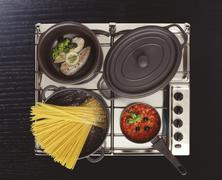 Stainless steel hob with boiling pasta water, fish in a pan, tomato sauce and Stock Photos