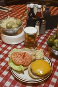 A cheeseburger, beer and pickled gherkins on a checked tablecloth Stock Photos
