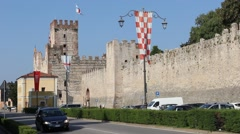 The Marostica castle (Castello Inferiore) with medieval flags and cars passing Stock Footage